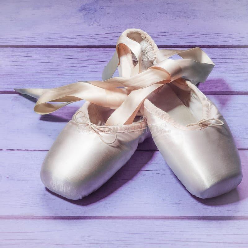 Pointe cal?a sapatas da dan?a do bailado com uma curva das fitas dobradas belamente em um fundo de madeira fotografia de stock royalty free