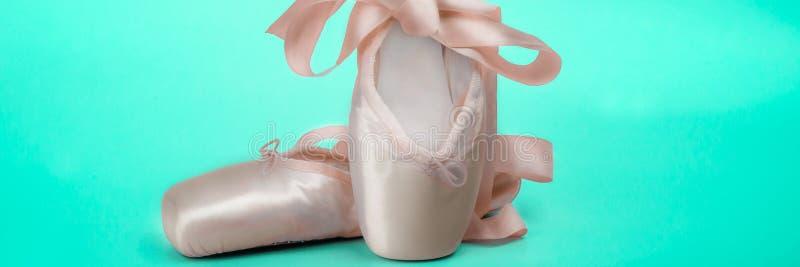 Pointe cal?a sapatas da dan?a do bailado com uma curva das fitas dobradas belamente em um fundo verde foto de stock