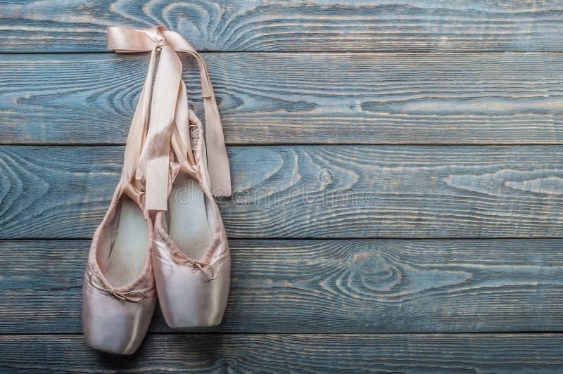 Pointe cal?a sapatas da dan?a do bailado com uma curva das fitas pendura em um prego em um fundo de madeira imagem de stock royalty free