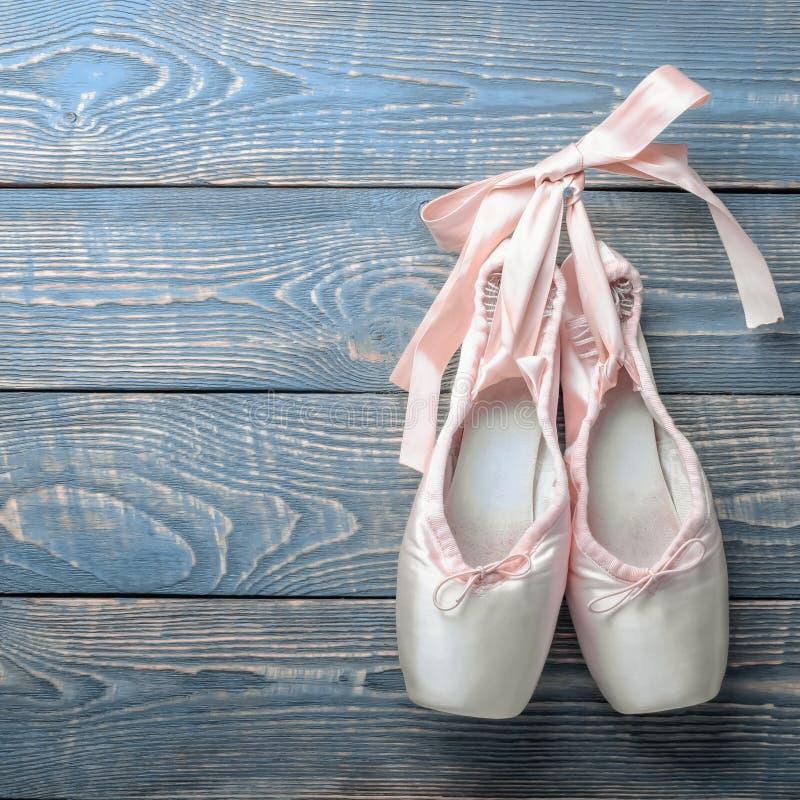 Pointe cal?a sapatas da dan?a do bailado com uma curva das fitas pendura em um prego em um fundo de madeira fotografia de stock royalty free