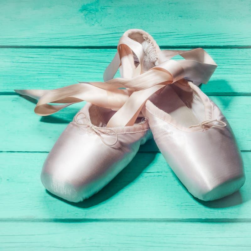 Pointe chausse des chaussures de danse de ballet avec un arc des rubans admirablement pli?s sur un fond en bois images stock