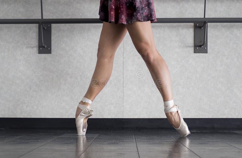 Pointe d'en de danseur classique dans des chaussures de pointe avec les jambes nues dans une jupe d'enveloppe pendant la classe d photo libre de droits