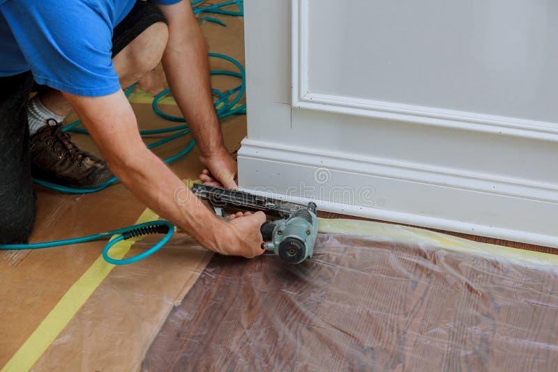 Pointe de charpentier utilisant l'arme à feu de clou à l'équilibre de moulage, avec l'étiquette de mise en garde que machines-out photographie stock