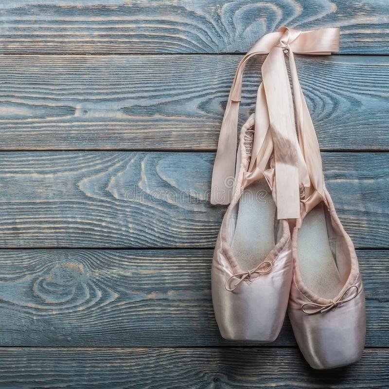 Pointe shoes ballet dance shoes with a bow of ribbons hang on a nail on a wooden background stock photos