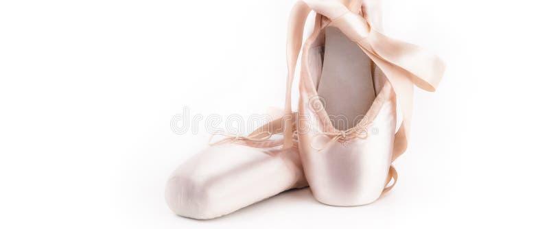 Pointe skor balettdansskor med en pilbåge av band beautifully vikta på en vit bakgrund med mycket ljus royaltyfri foto