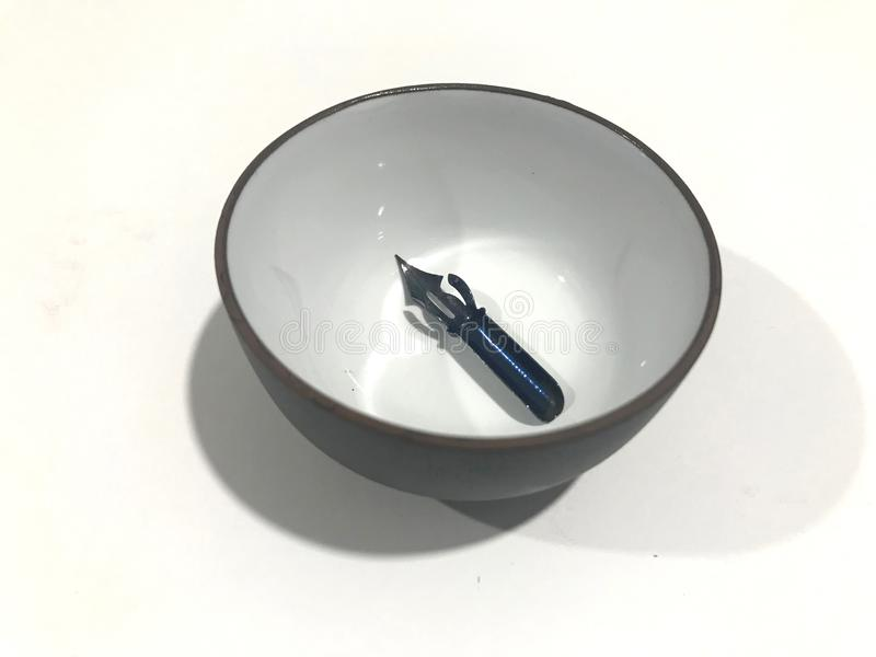 Pointed nib inside an ink bowl. Used vintage metallic manual nib used for manuscript and scribing letters ready for cleaning royalty free stock photo
