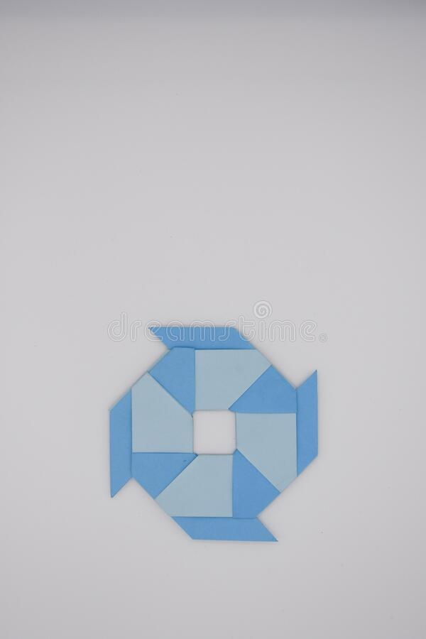 8 pointed ninja star paper fold. One blue paper fold of 8 pointed ninja star was taken royalty free stock photos