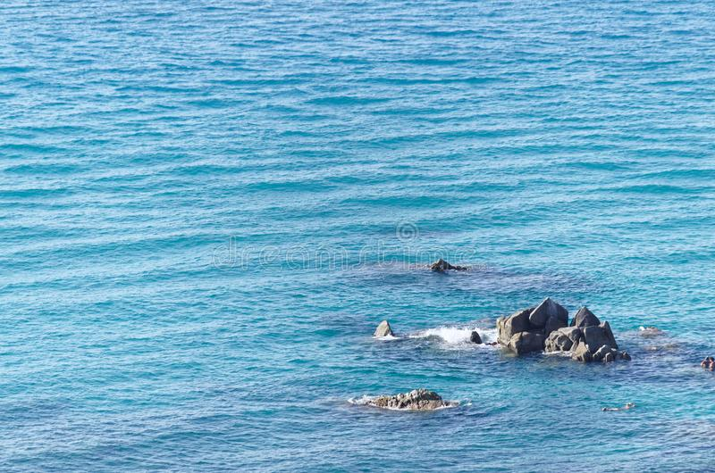 Pointed rocks in the blue water of tyrrhenian sea. Near a Riaci beach in Tropea, Italy royalty free stock photo