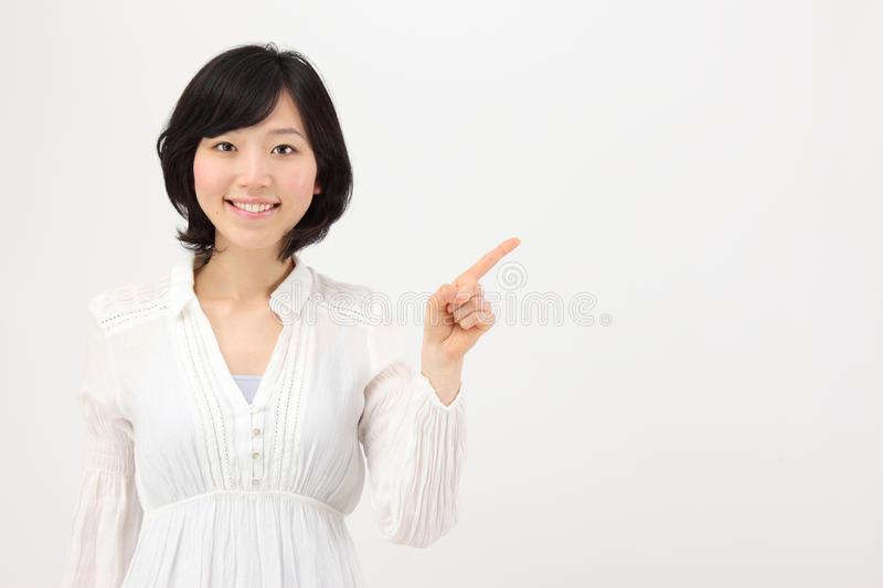 Pointed to a young asian woman. Pointed to a young japanese woman in white background royalty free stock images