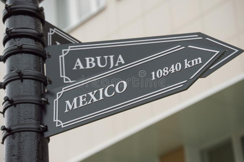 Pointer cities on the post/ Abuja, Nigeria, Africa and  Mexico c. Pointer cities on the post. Abuja, Nigeria, Africa and Mexico city, Mexico. Distance to these stock photo