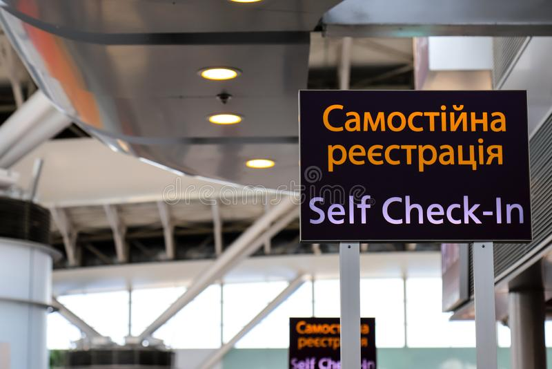 Pointer with an inscription in the Ukrainian - Self check-in at the airport. Information stand, self registration panel stock image
