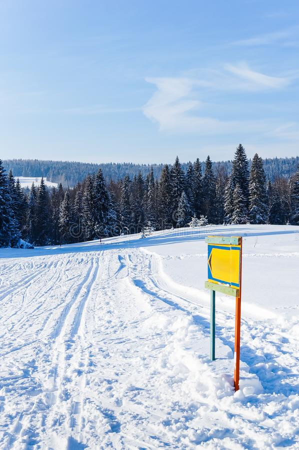 A pointer to the ski run in the winter forest under the blue sky royalty free stock photos