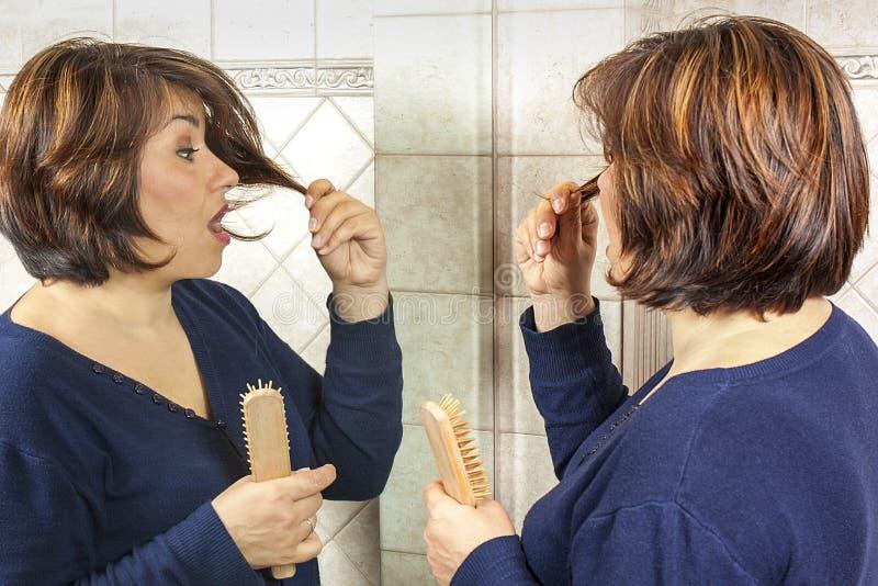 Pointes fourchues étonnées par miroir de femme de brosse de cheveux photographie stock