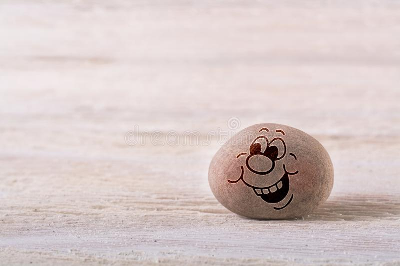 Pointing emoticon. Stone face on white wood background with free space for your text stock photo