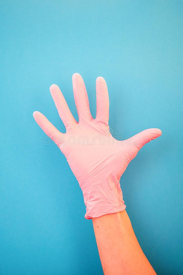 Pointing a finger at number five, wearing pink medical gloves, against a blue background. Good habits, vaccination, medical store. Pharmacy stock image
