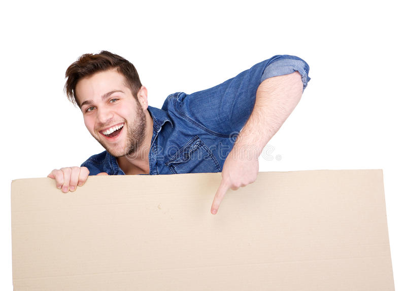 Pointing finger to blank poster sign. Portrait of a happy young man smiling and pointing finger to copy space on blank poster sign royalty free stock images