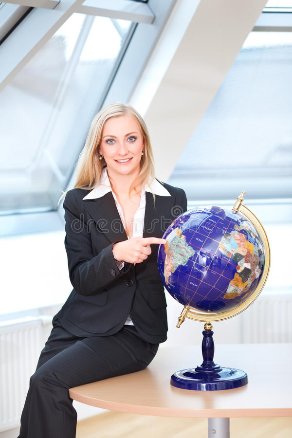 Pointing on the globe. Woman in charge is pointing on the globe royalty free stock image