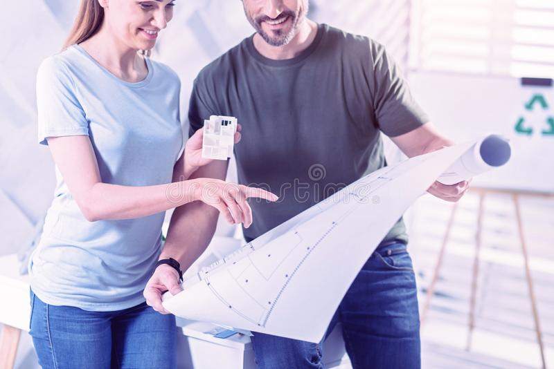 Happy architect holding miniature house and pointing to the blueprint stock photos