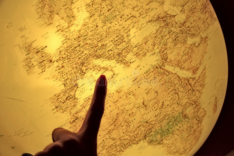 Pointing at Italy on globe. Image of a backlit globe with a finger pointing at Italy royalty free stock image