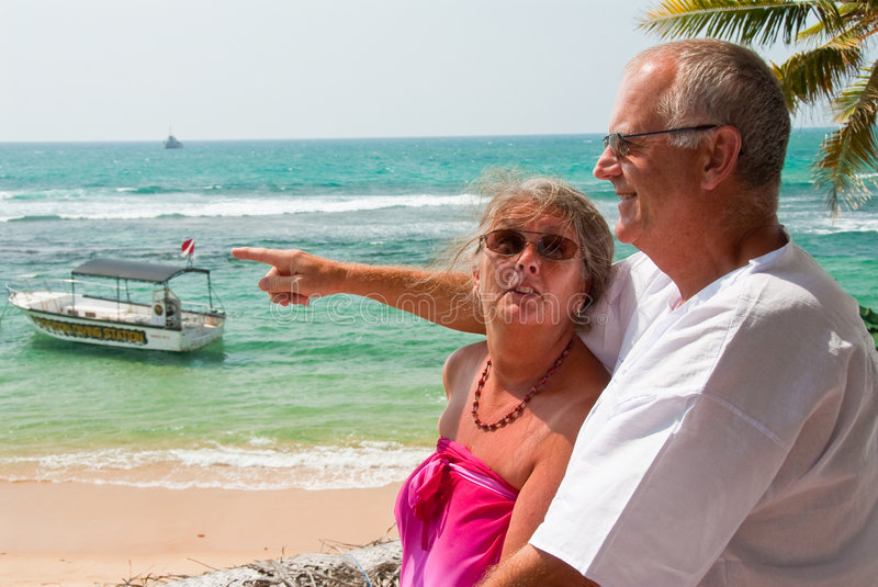 Pointing mature couple by ocean