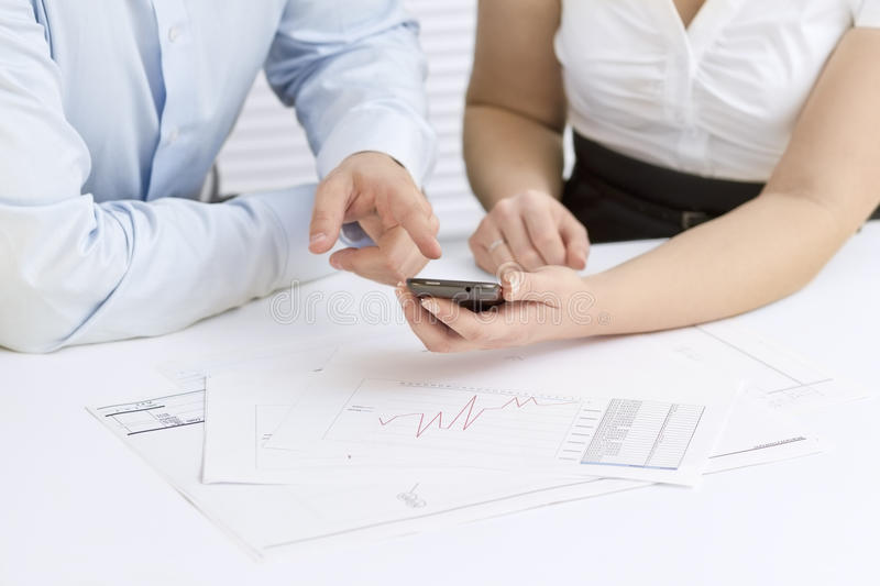 Pointing at Smartphone in Business Meeting. A businesswoman and a businessman in a meeting. Teamwork. Pointing and looking at a mobile phone stock photo