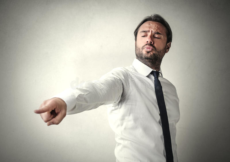 Pointing at someone. Elegant buinessman pointing at someone stock photos