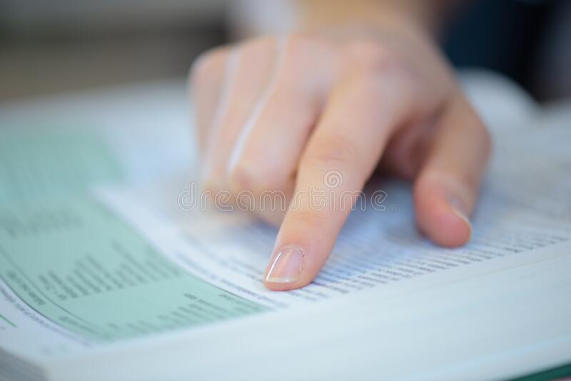 Pointing at specific word on book. Pointing at the specific word on the book royalty free stock photos