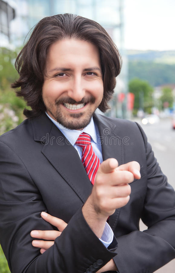 Pointing turkish businessman with suit in front of his office. With the building in the background royalty free stock images