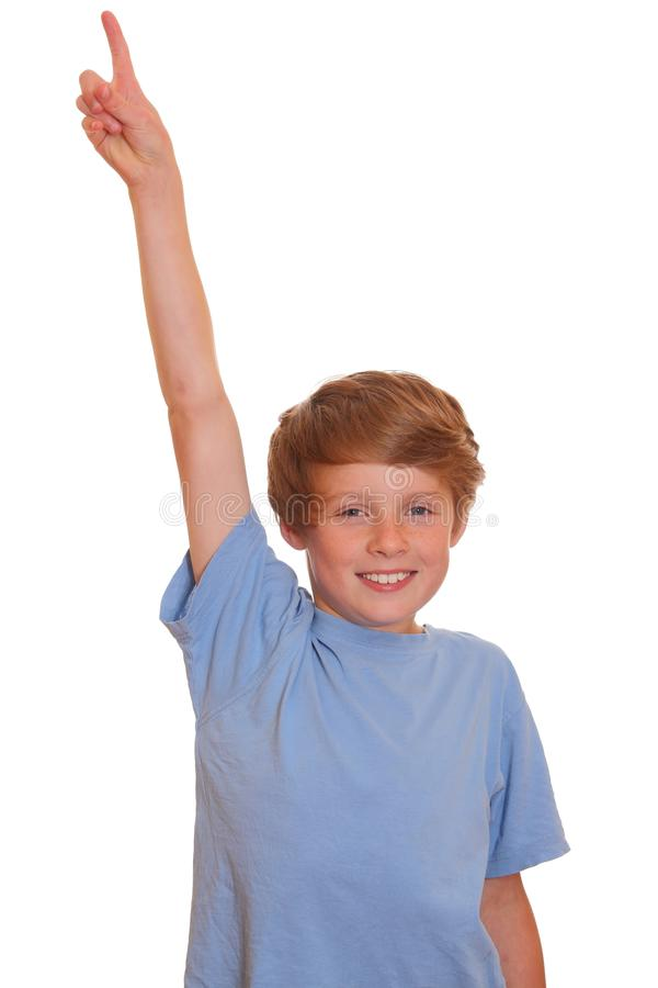 Pointing upward. Portrait of a happy young boy pointing upward on white background royalty free stock image