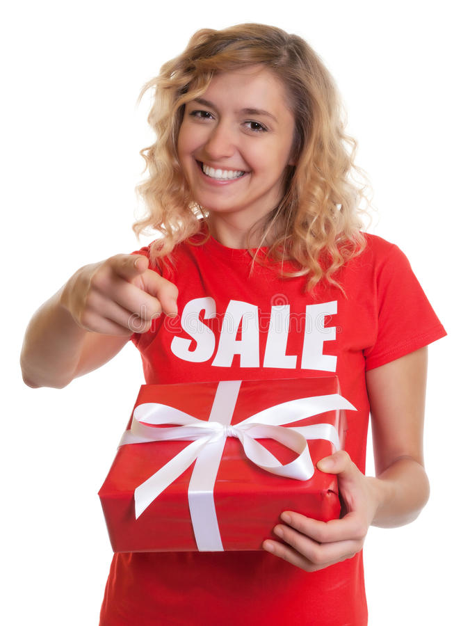 Pointing woman with blond hair and gift in a sales-shirt. On an isolated white background for cut out stock image