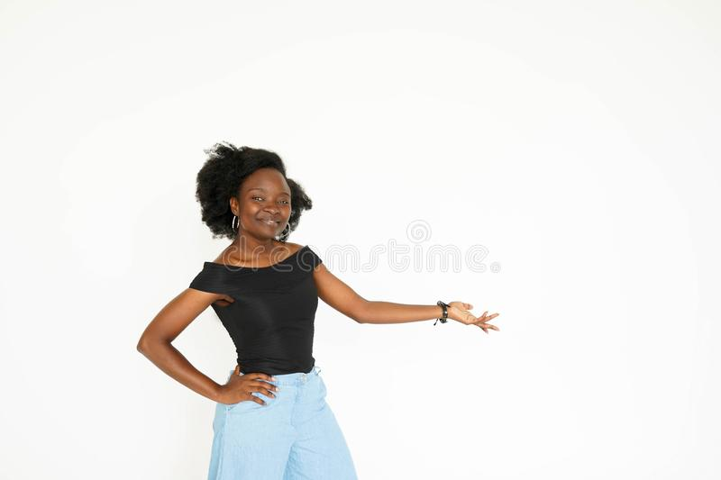 Pointing you advertising. Attractive young African woman pointing away and smiling while standing isolated on white stock images