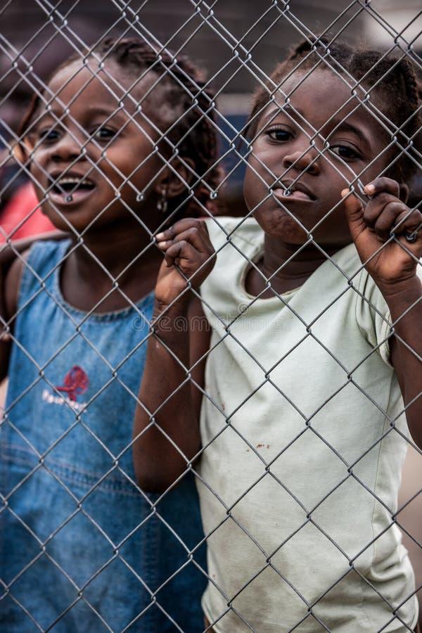 POINTNOIRE/CONGO - 18 MAGGIO 2013 - bambini africani dietro sorridere della griglia del metallo fotografia stock