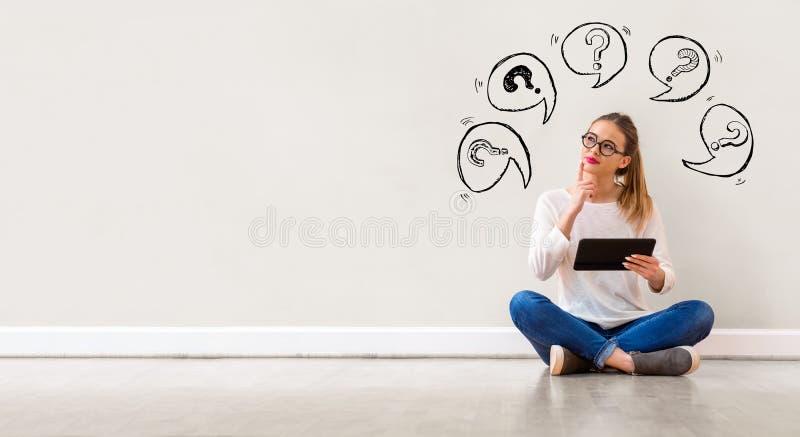 Points d'interrogation avec des bulles de la parole avec la femme à l'aide d'un comprimé photo libre de droits