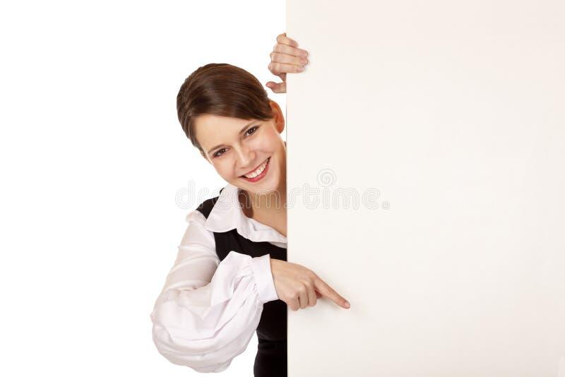 Points de femme avec le doigt sur le panneau-réclame blanc images stock