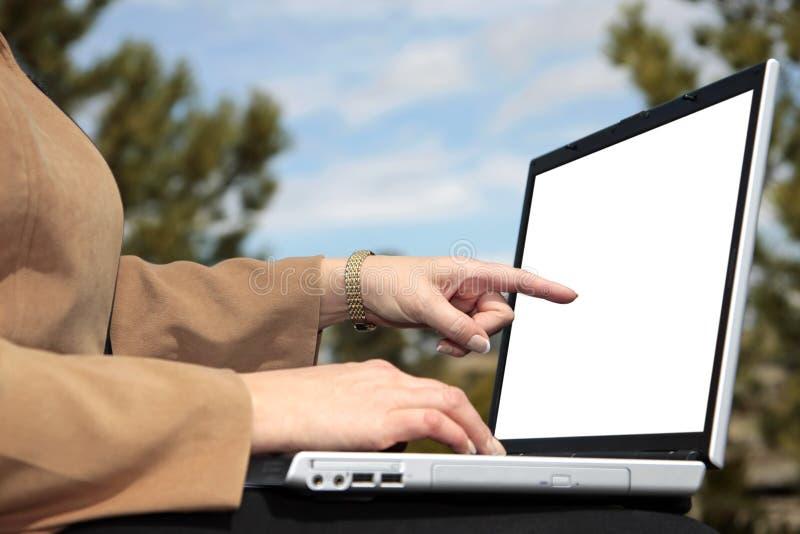 Points de femme d'affaires à l'écran blanc d'ordinateur portatif image stock