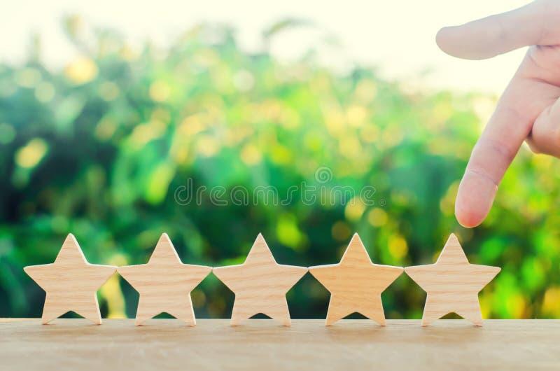 Points de main à la cinquième étoile en bois Obtenez la cinquième étoile Le concept de l'estimation des hôtels et des restaurants photographie stock