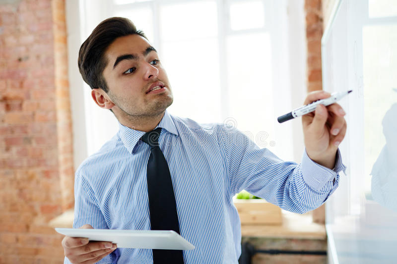 Points of project. Confident trader writing down his ideas on whiteboard royalty free stock image
