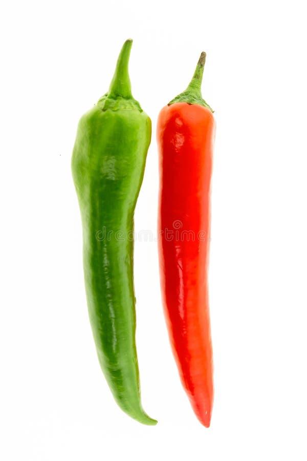 Pointu lumineux de piment de poivrons de cosse de légumes verts rouges mûrs de parallèle sur le fond blanc de conception de fond images stock