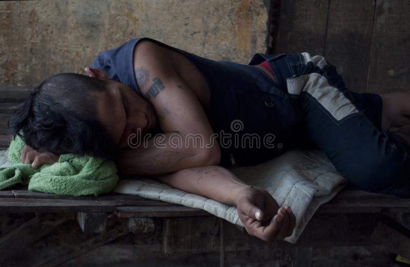Poipet/Cambodge - 05 04 2012 : Le jeune homme sans abri malade prend un petit somme à la station de train abandonnée photographie stock