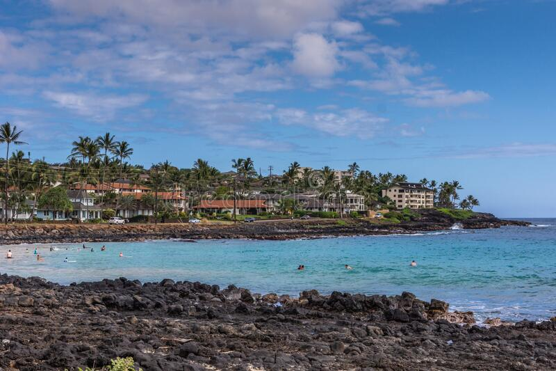 Brenneckes beach and bay at Poipu shores, Kauai, Hawaii, USA. Poipu, Kauai, Hawaii, USA. - January 11, 2012: Black rocks form Brenneckes beash and bay with blue stock images