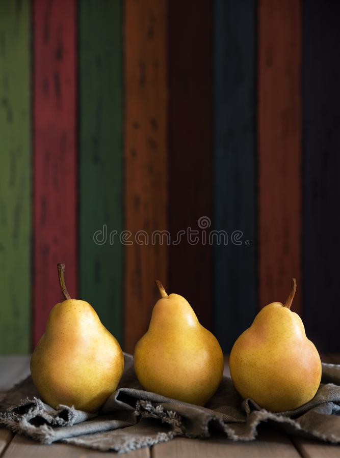 Poire jaune délicieuse Williams sur un fond en bois des conseils en bois colorés Illustration pour annoncer le jus de poire image libre de droits