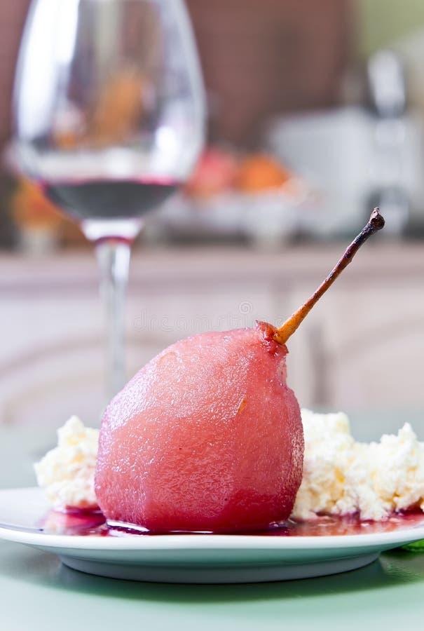 Poire pochée avec de la sauce à vin rouge photographie stock