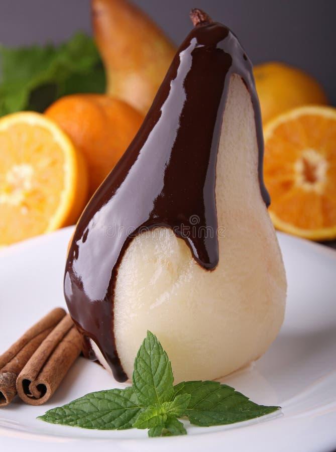 Poire pochée avec du chocolat images stock