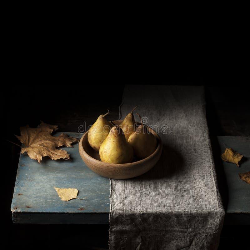 Poire sur la table dans un plat en bois Serviette tissée photo stock