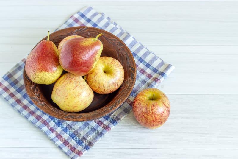 Poires et pomme rouges dans le plat brun sur la table en bois blanche image libre de droits