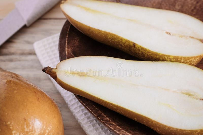 Poires mûres de plan rapproché d'un plat en bois de cru sur la table, dessert doux de fruit, récolte d'automne, produits de régim photos stock