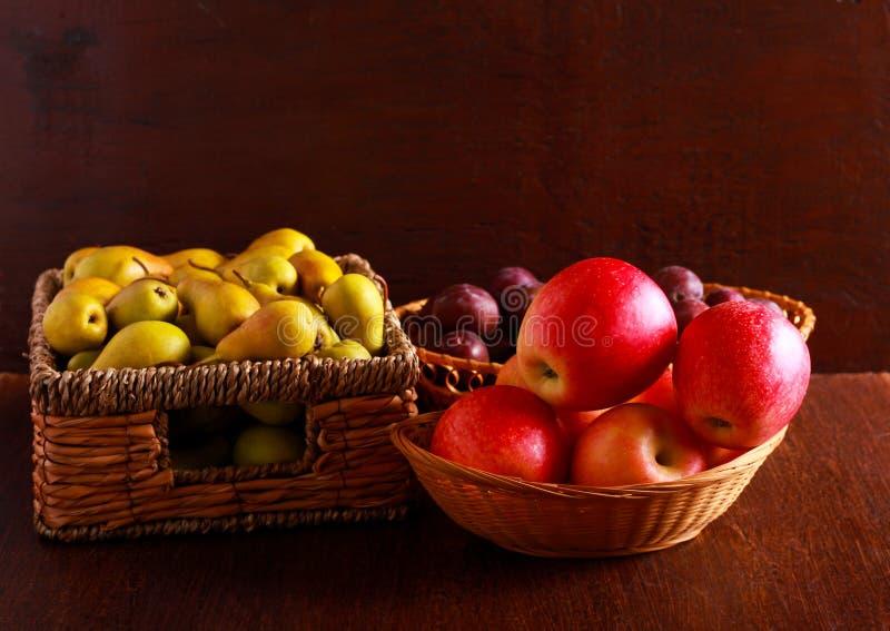 Poires, pommes et prunes dans les paniers photographie stock libre de droits