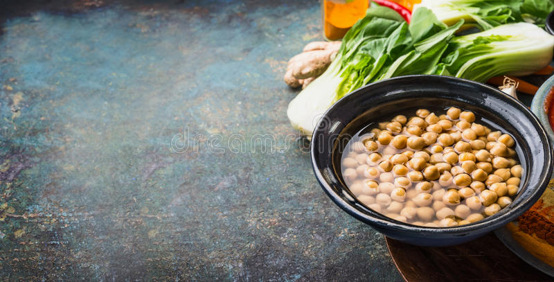Pois chiches cuits dans la cuvette avec le végétarien faisant cuire des ingrédients sur le fond rustique, endroit pour le texte,  photographie stock libre de droits