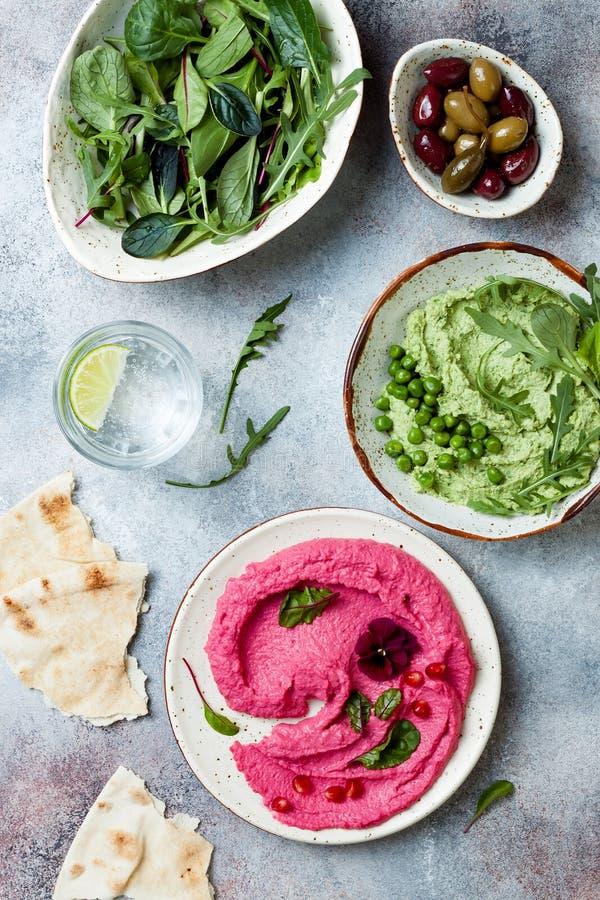 Pois et diffusion ou immersion rose de houmous de betterave avec des feuilles de salade de mélange r photos libres de droits
