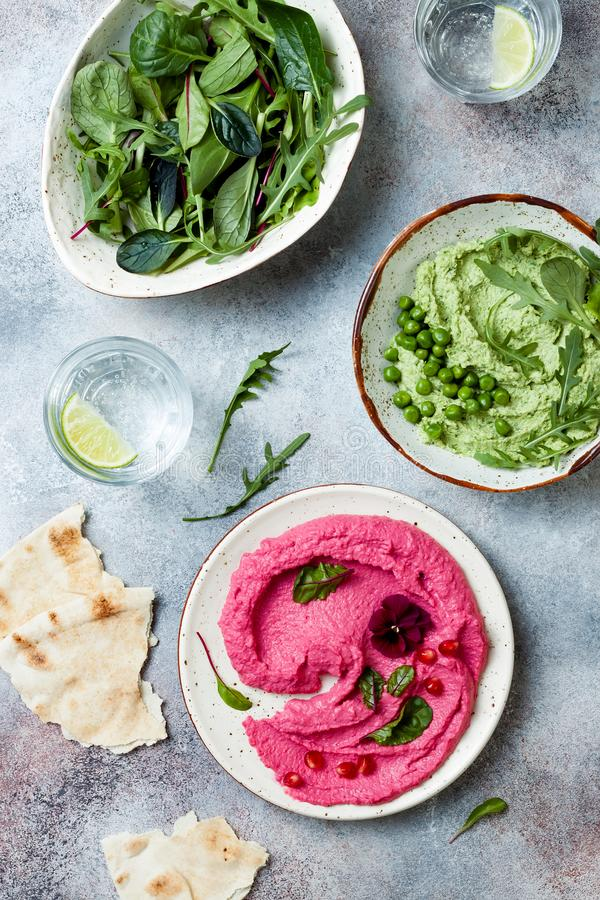 Pois et diffusion ou immersion rose de houmous de betterave avec des feuilles de salade de mélange r photographie stock libre de droits